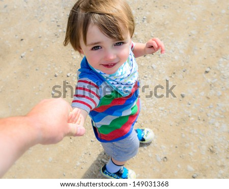 A beautiful little boy walking and looking up at his parent, holding hands