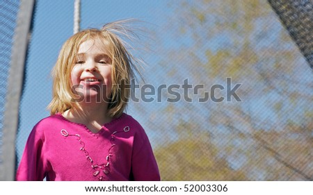 A beautiful little girl enjoying the Spring sunshine in her trampoline, with room for text.