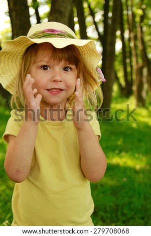 a beautiful little girl in a hat on the nature - stock photo