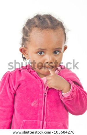 A beautiful little girl in a playful mood a finger in her mouth - stock photo