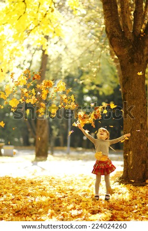 a beautiful little girl in the autumn park playing in nature - stock photo