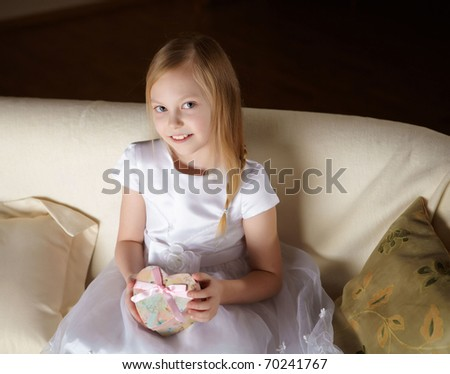 a beautiful little girl in white dress sitting on a sofa with a present at home - stock photo