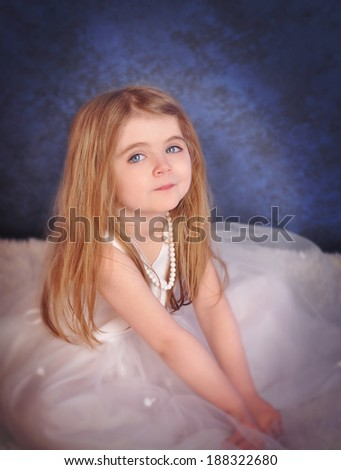 A beautiful little girl is dressed up in a glamorous white dress sitting down on a blue background for a fashion or wedding concept. - stock photo