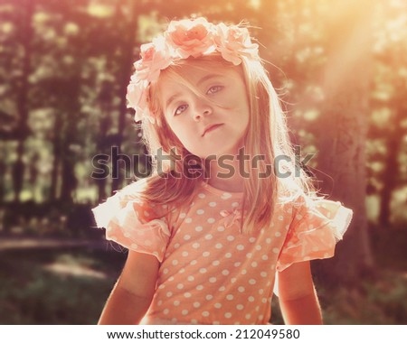 A beautiful little girl is wearing a pink flower crown in the woods with bright sunshine on her face for a peace or nature concept. - stock photo