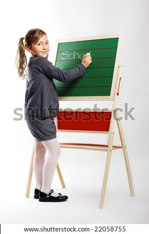 a beautiful little girl is writing the word school on a board - stock photo
