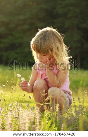 a beautiful little girl playing in nature - stock photo