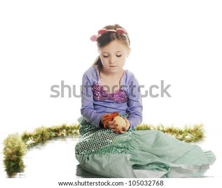 A beautiful little mermaid carefully holding a hermit crab.  On a white background. - stock photo