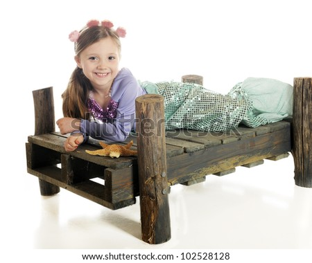 A beautiful little mermaid happily laying on a rustic wood dock with a star fish.  On a white background. - stock photo