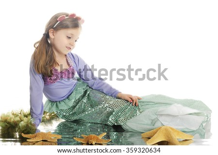 A beautiful little mermaid relaxed among starfish and seaweed, with a watery reflection.  On a white background. - stock photo