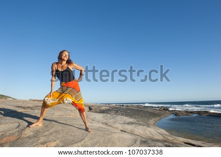 A beautiful looking middle aged woman is standing confident, happy and relaxed smiling on rocks at ocean, isolated with sea and blue sky as background and copy space. - stock photo