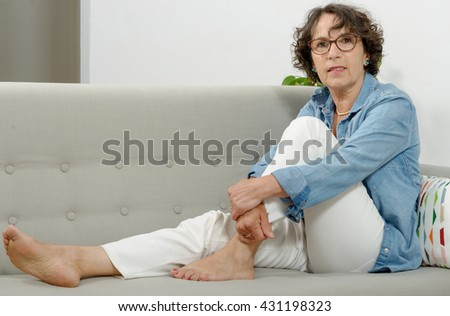 a beautiful mature woman lying on the couch