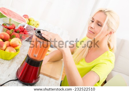 A beautiful mature woman preparing a smoothie or juice with fruits in the kitchen.  - stock photo