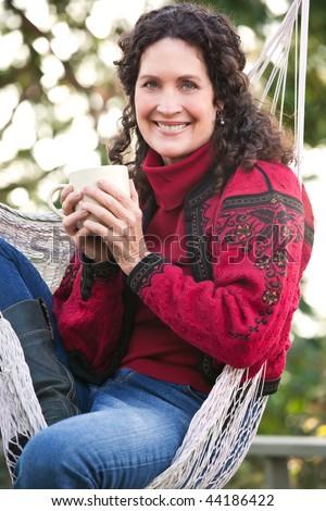 A beautiful mature woman sitting on a hammock drinking coffee - stock photo