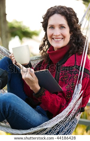 A beautiful mature woman sitting on a hammock reading a book