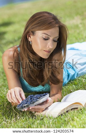 A beautiful middle aged woman in her thirties laying down outside on grass eating blueberries and reading a book - stock photo