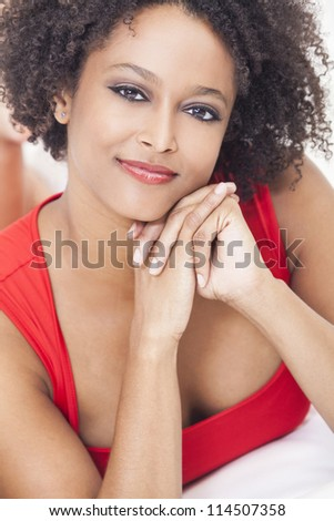 A beautiful mixed race African American girl or young woman laying down wearing a red dress - stock photo
