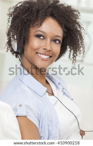 A beautiful mixed race African American girl or young woman listening to music on mp3 player and headphones - stock photo