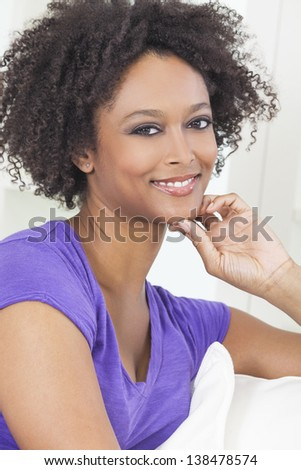 A beautiful mixed race African American girl or young woman looking happy and thoughtful - stock photo