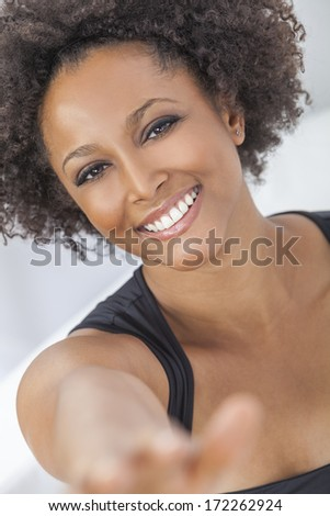 A beautiful mixed race African American girl or young woman looking happy reaching to the camera