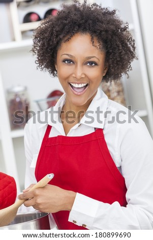 A beautiful mixed race African American girl or young woman looking happy wearing a red apron & cooking in her kitchen at home - stock photo