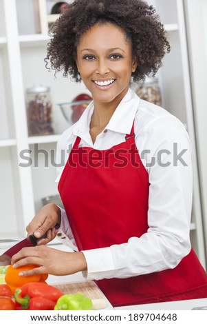 A beautiful mixed race African American girl or young woman looking happy wearing red apron, chopping vegetables & cooking in her kitchen at home - stock photo