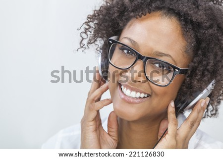 A beautiful mixed race African American girl or young woman wearing glasses and listening to music on mp3 player and headphones - stock photo