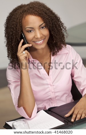 A beautiful mixed race African American girl, possibly a student or businesswoman sitting at a desk talking on her cell phone.