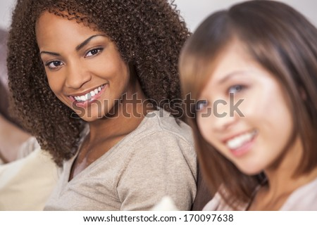 A beautiful mixed race African American girl smiling with her Chinese Asian friend - stock photo
