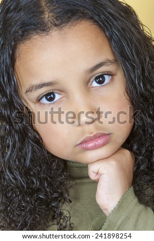 A beautiful mixed race African American little girl female child looking sad and sulking - stock photo