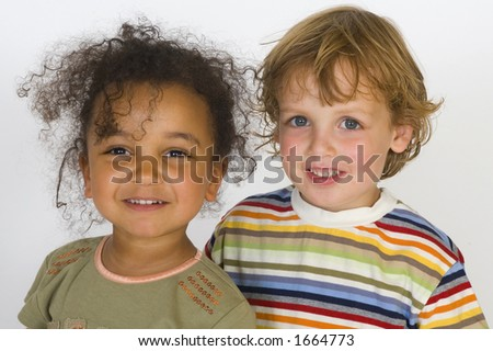 A beautiful mixed race girl and a blonde boy stand together - stock photo