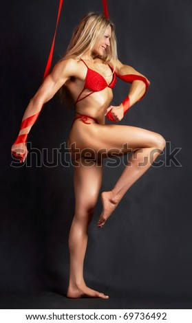 A beautiful model in red bikini marching to the right with red ribbons wound round her arms