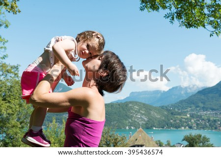 a beautiful mom is a hug to her daughter in nature - stock photo