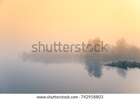 A beautiful morning scenery at the lake in Norway. Tranquil autumn landscape. Rock formation in a foreground. Colorful landscape with mist.