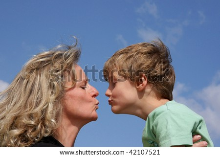 a beautiful mother giving a kiss to her cute 7-years old son photographed in the summer sun with blue sky and clouds in the background