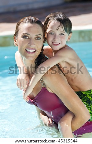 A beautiful mother having fun with her son on her shoulders in a swimming pool