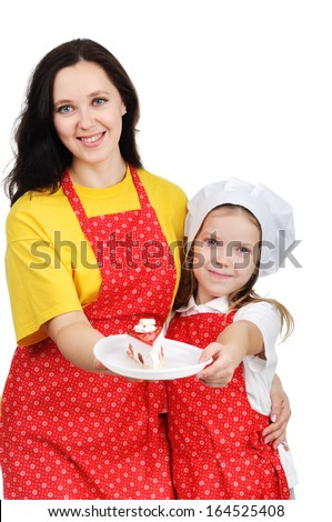 A beautiful mother holding a plate with cake hugging her daughter. - stock photo