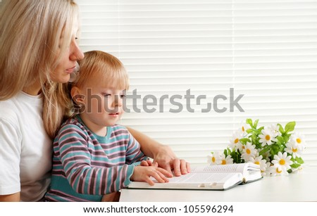 A beautiful mother with her daughter with a book on a light background