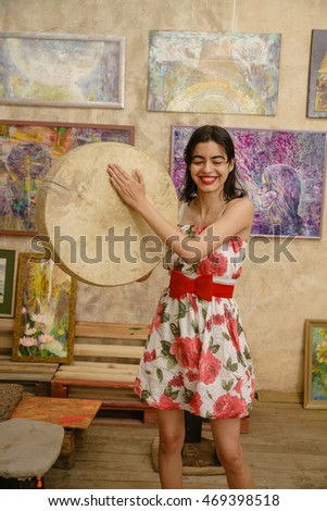 A beautiful mysterious girl is playing a tambourine against the colorful background