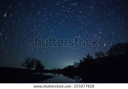 a beautiful night sky, Milky Way, star trails  and the trees - stock photo
