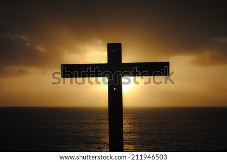A beautiful photo in which the cross cover the light of the sun in a sunset over the sea