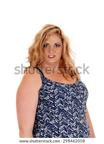 A beautiful plus sized young woman in a blue and white dress standing