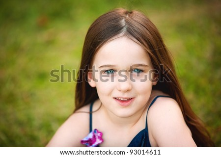 A beautiful portrait of a young brunette six year old in the outdoors - stock photo