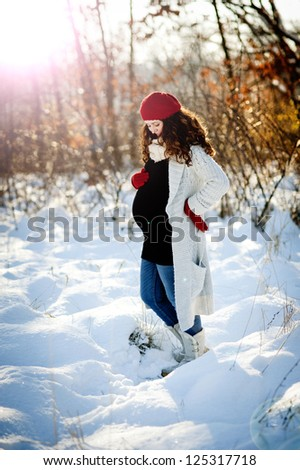 A beautiful pregnant woman is playing outside in the snow - stock photo