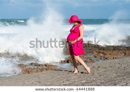 A beautiful pregnant woman standing on the beach in a pink sundress and hat with the ocean waves crashing behind her. - stock photo