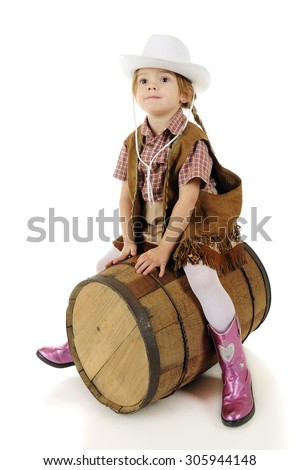 A beautiful preschool cowgirl straddling a rustic barrel as if it were a horse.  On a white background. - stock photo