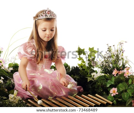 A beautiful preschool princess playing xylophone pipes while surrounded by flowers and foliage. - stock photo