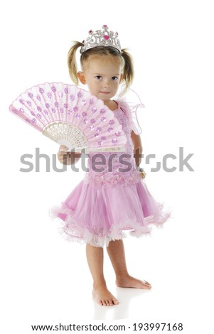 A beautiful preschooler dressed as a princes in pink, shyly holding an opened sparkly-pink fan.  On a white background. - stock photo