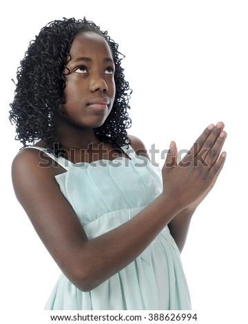 A beautiful preteen looking heavenward as she prays with clasped hands.  On a white background.