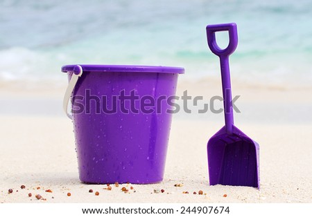 A beautiful Purple bucket and spade on an isolated tropical beach - stock photo