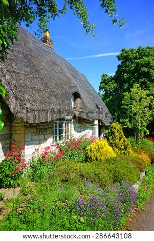 A beautiful quaint Cotswold country Cottage and garden in summer with blue sky and clouds, in the heart of The Cotswolds, Gloucestershire, United Kingdom - stock photo
